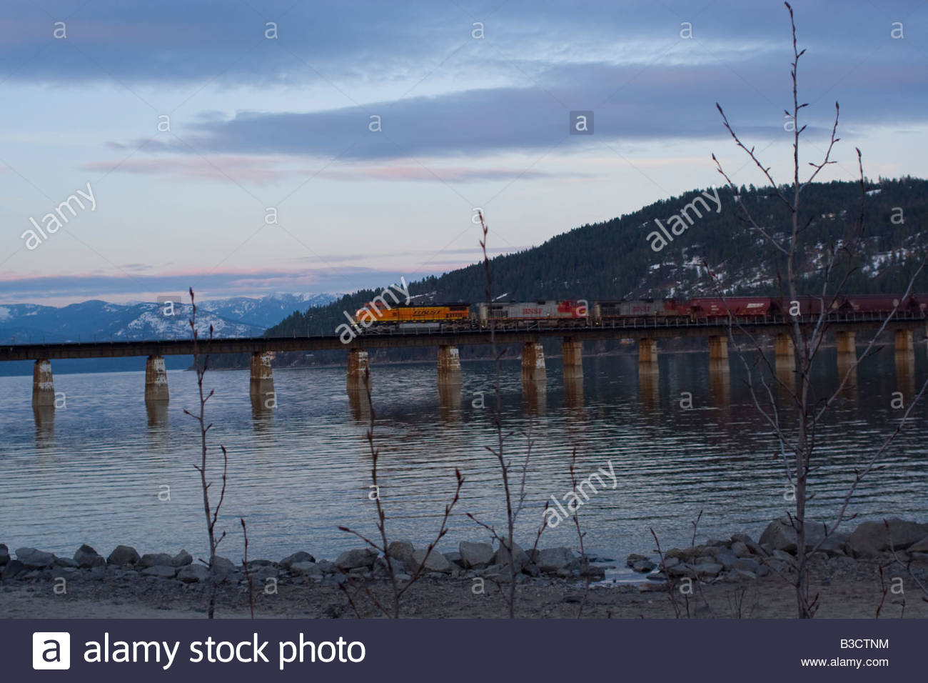 A train seen crossing the 8000 foot long BNSF Railroad bridge on Lake Pend Oreille at Sandpoint Idaho - Stock Image
