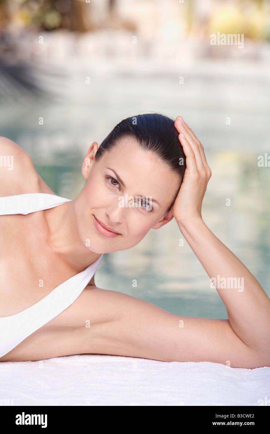 Young woman relaxing on pool side, portrait - Stock Image