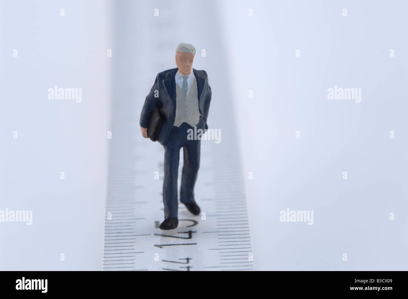 Business man figurine on measuring tape - Stock Image