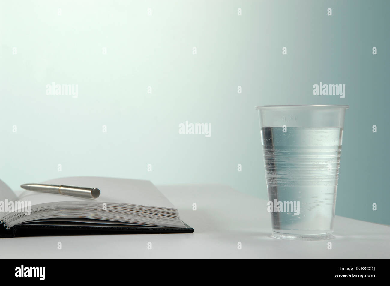 Glass of water with pen and notebook - Stock Image