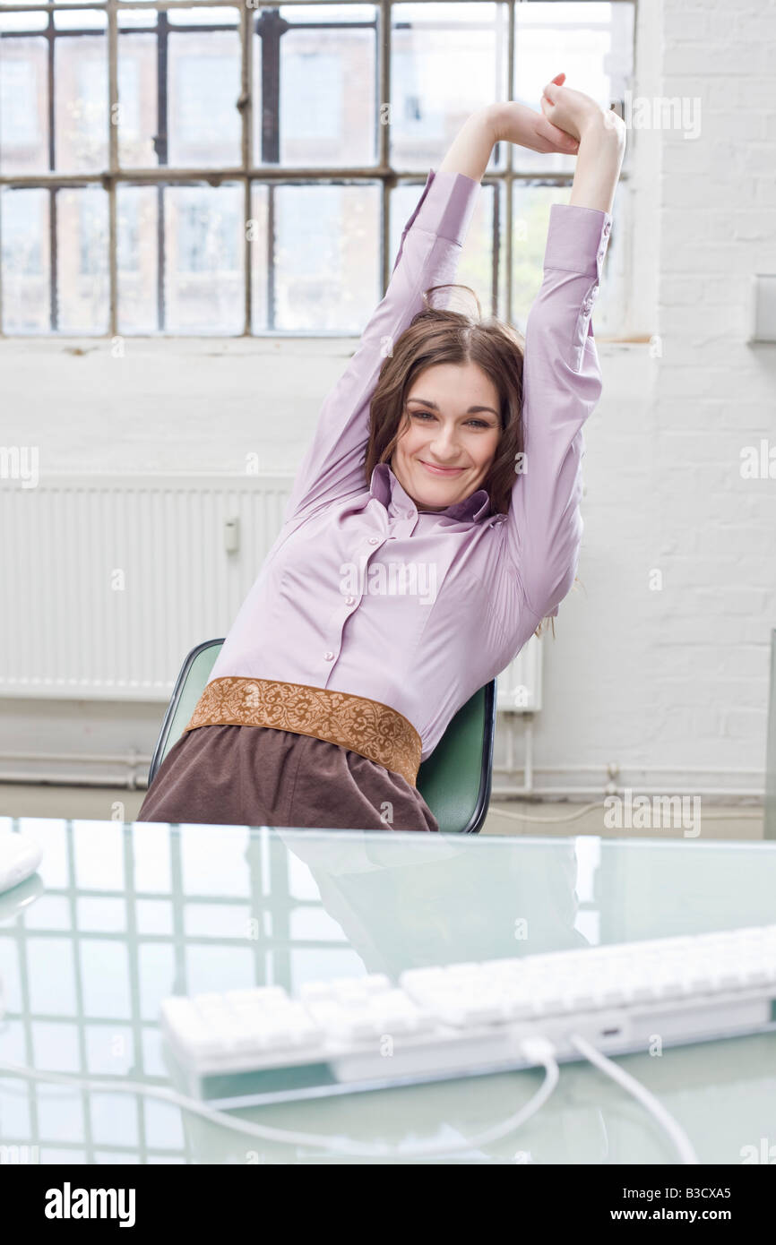 Young businesswoman in office, relaxing - Stock Image