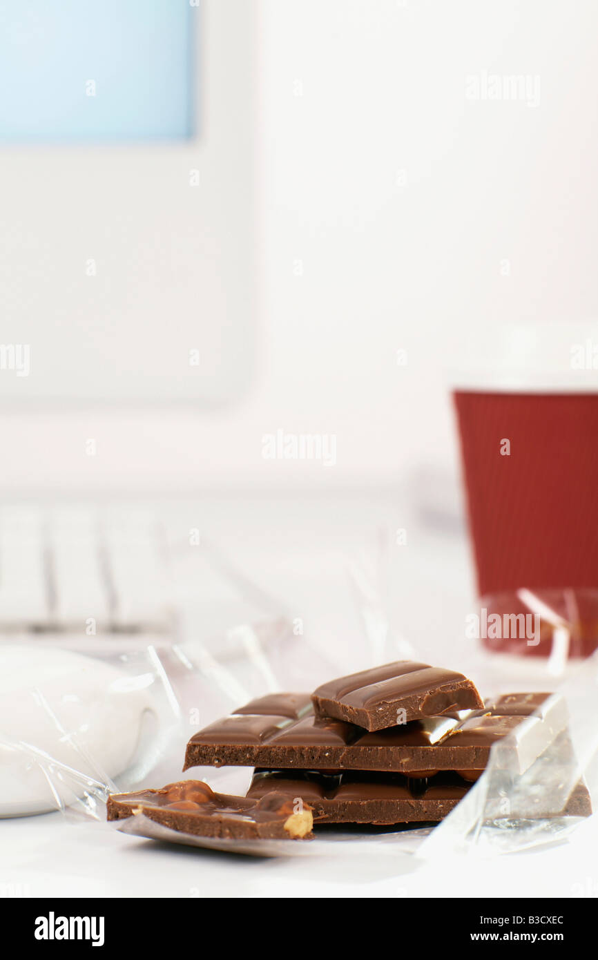 Pieces of chocolate on office desk - Stock Image