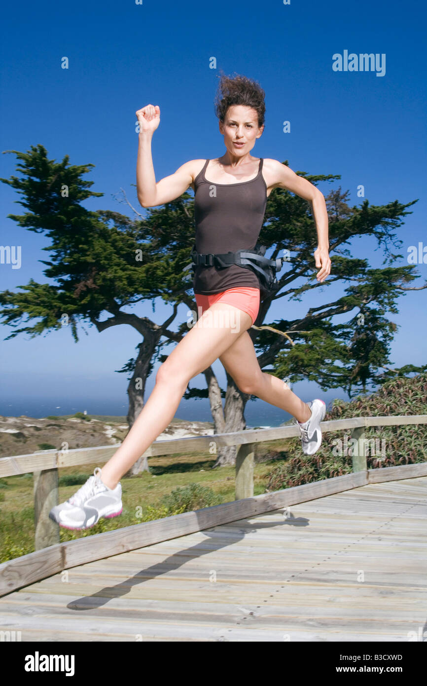 South Africa, Cape Town, Young woman jumping, portrait - Stock Image
