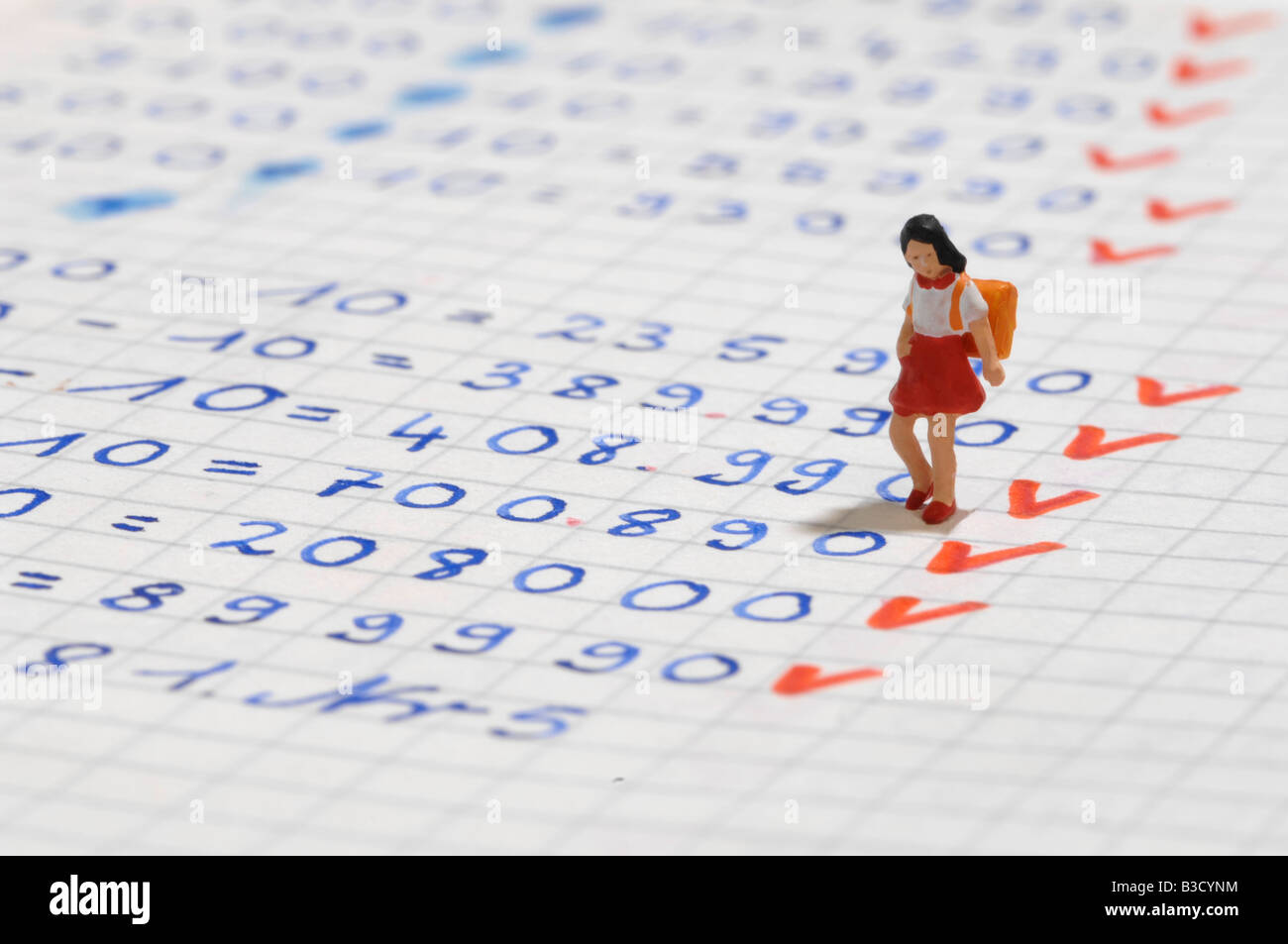Figurine of Schoolgirl on exercise book - Stock Image