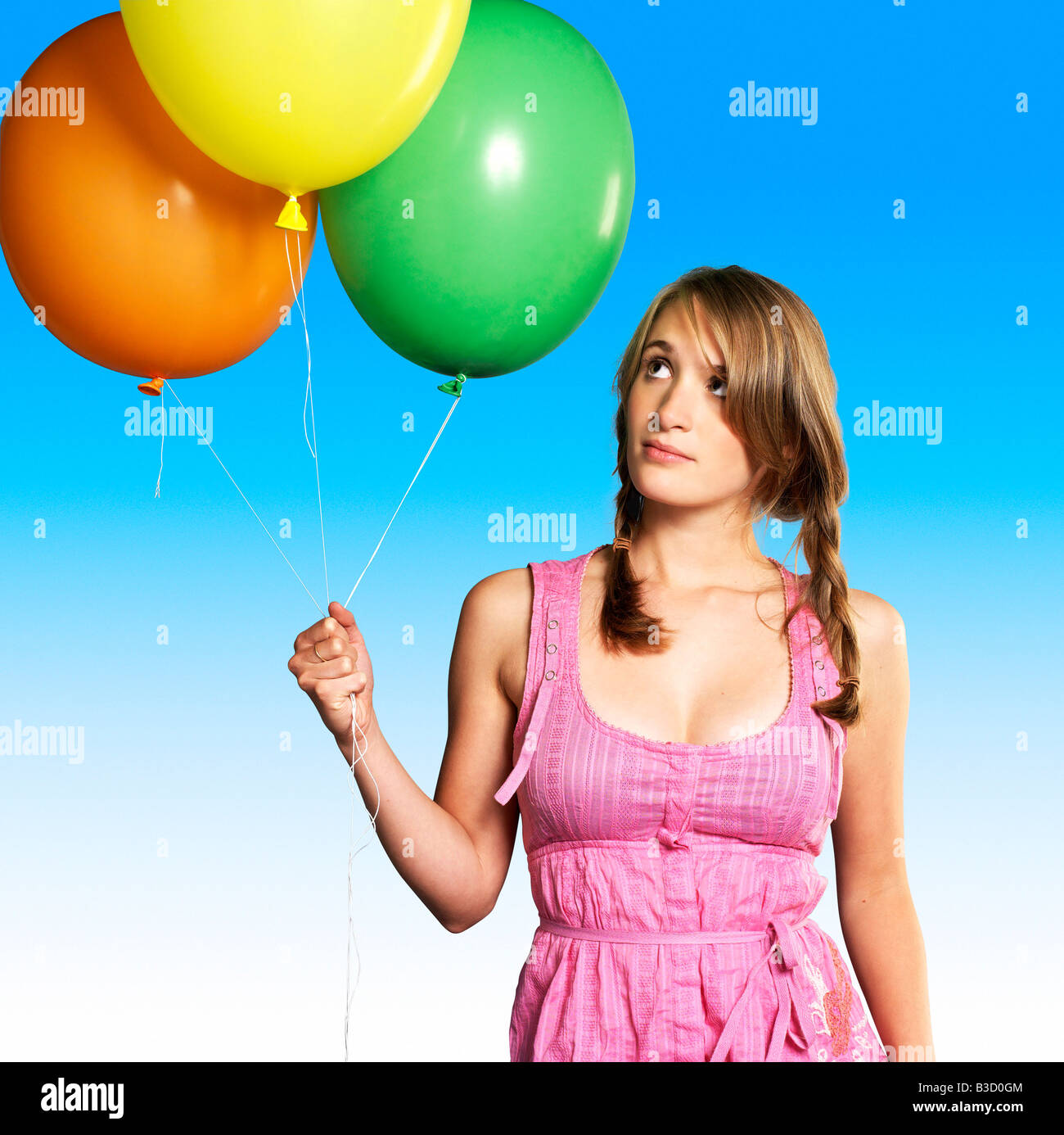 Teenage girl (16-17) holding bunch of balloons, portrait - Stock Image
