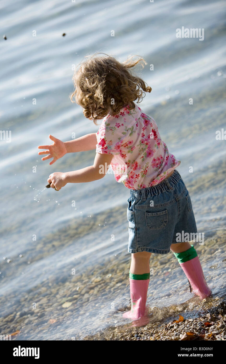 Germany, Bavaria, Ammersee, little girl (3-4) playing on beach - Stock Image