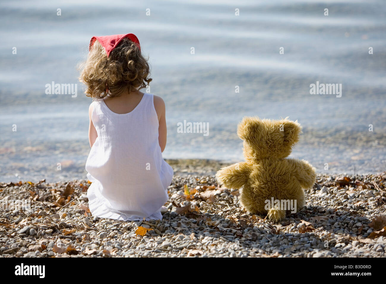 Germany, Bavaria, Ammersee, little girl (3-4) sitting on beach, rear view - Stock Image
