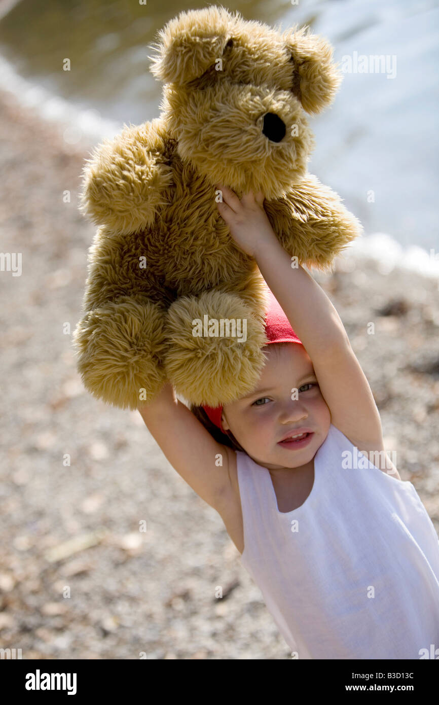 Germany, Bavaria, Ammersee, little girl (3-4) lifting teddy bear - Stock Image