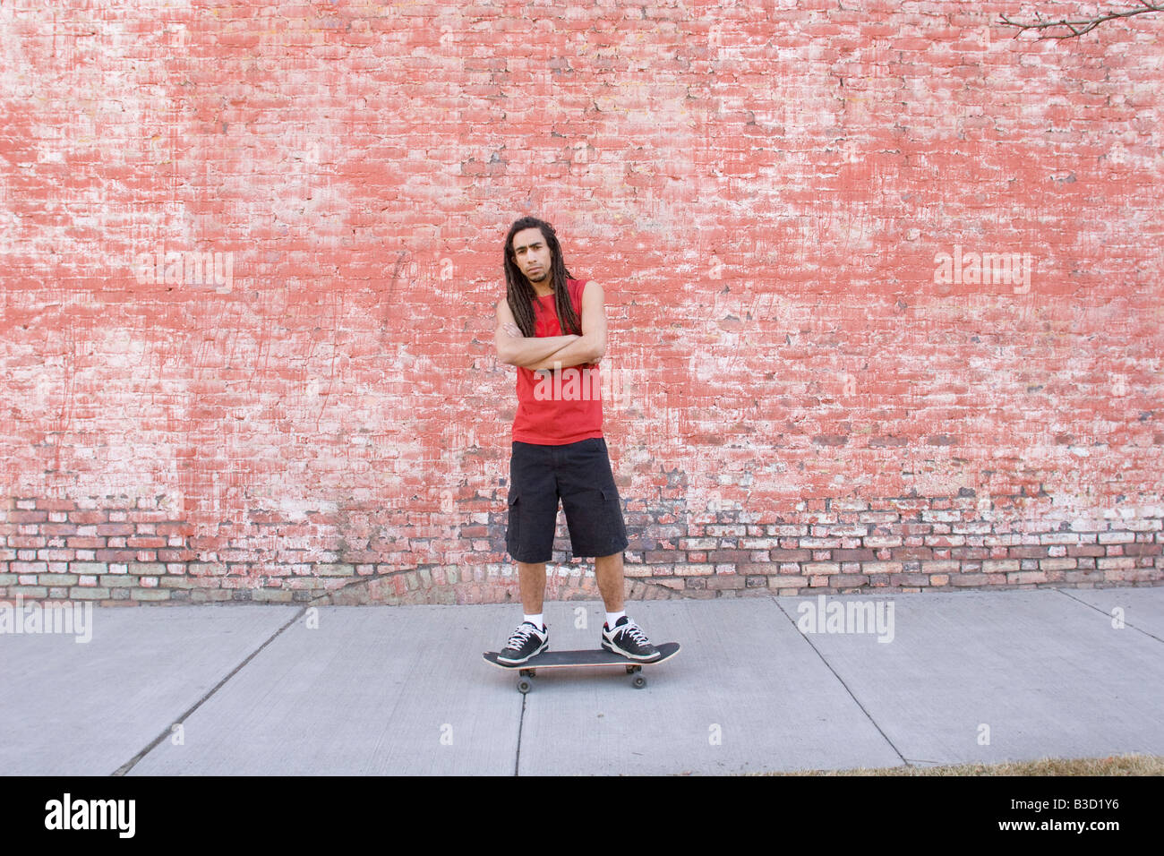 Young man standing on skateboard, portrait - Stock Image