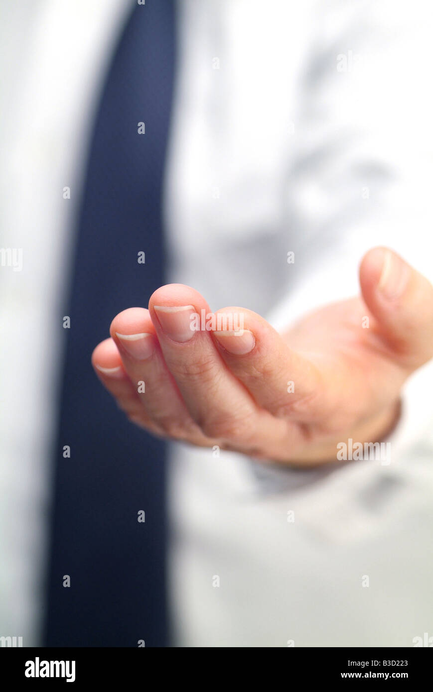Businessman holding out an open, empty left hand towards camera - Stock Image