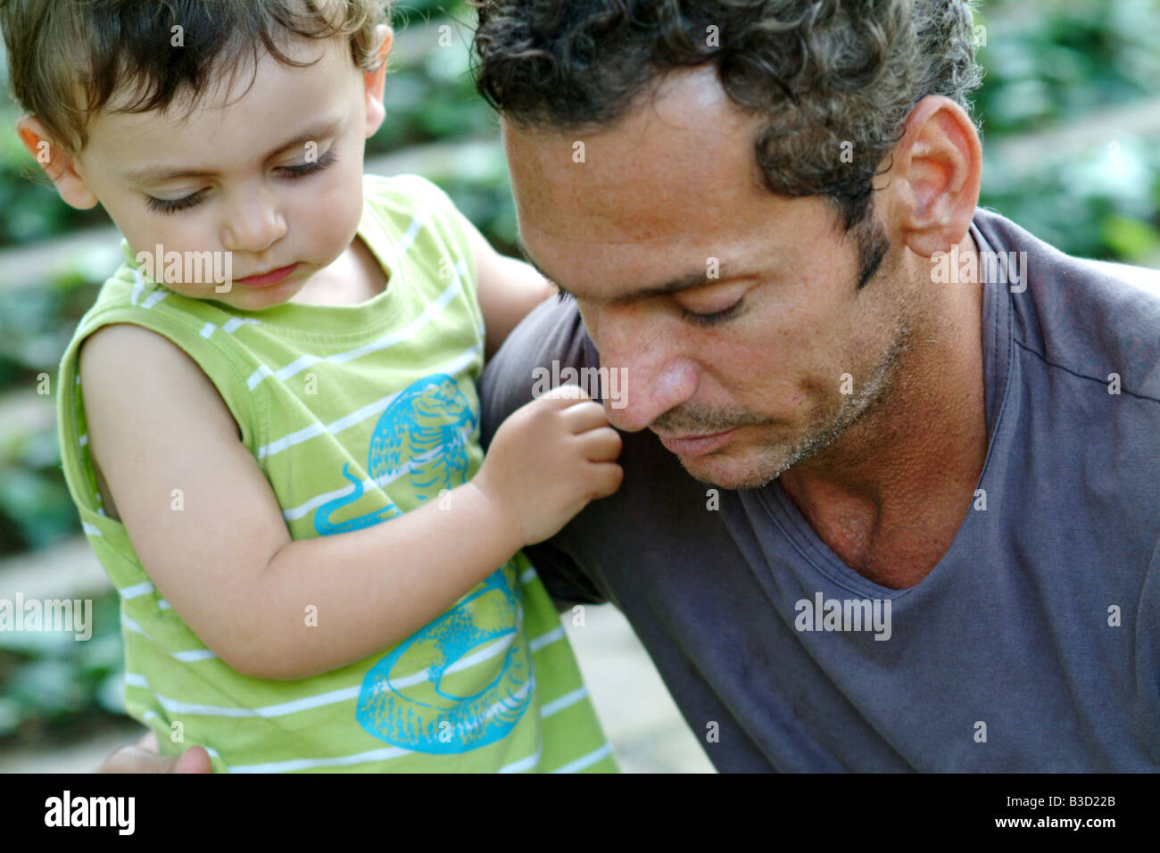 a father and his toddler son play together in the park on a spring day - Stock Image