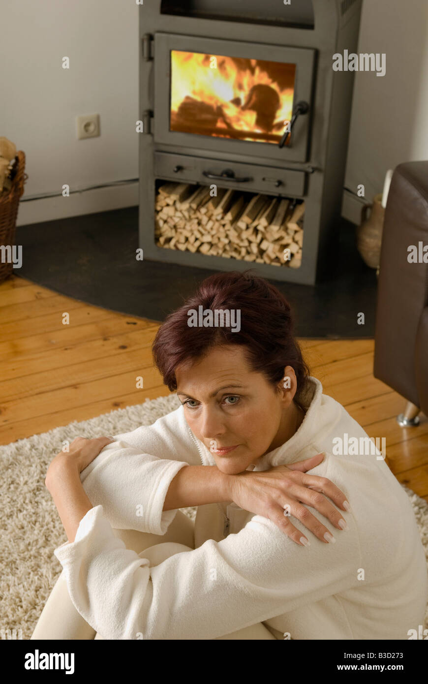 Brunette woman sitting in living room, elevated view - Stock Image