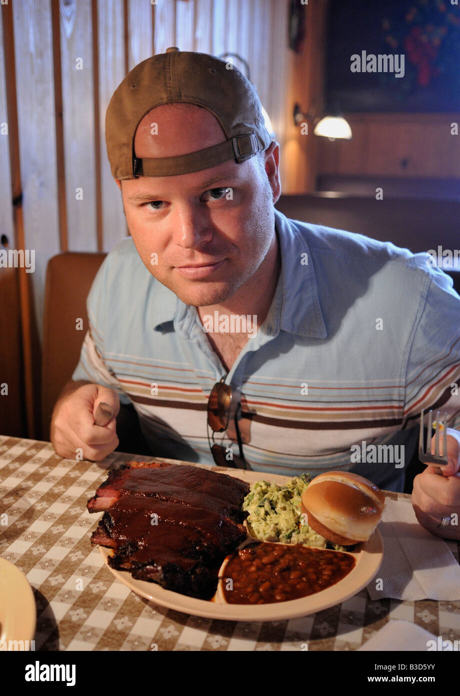 A man prepares to eat barbequed pork ribs, baked beans, and coleslaw at Neely's Bar-B-Que restaurant in Memphis, - Stock Image
