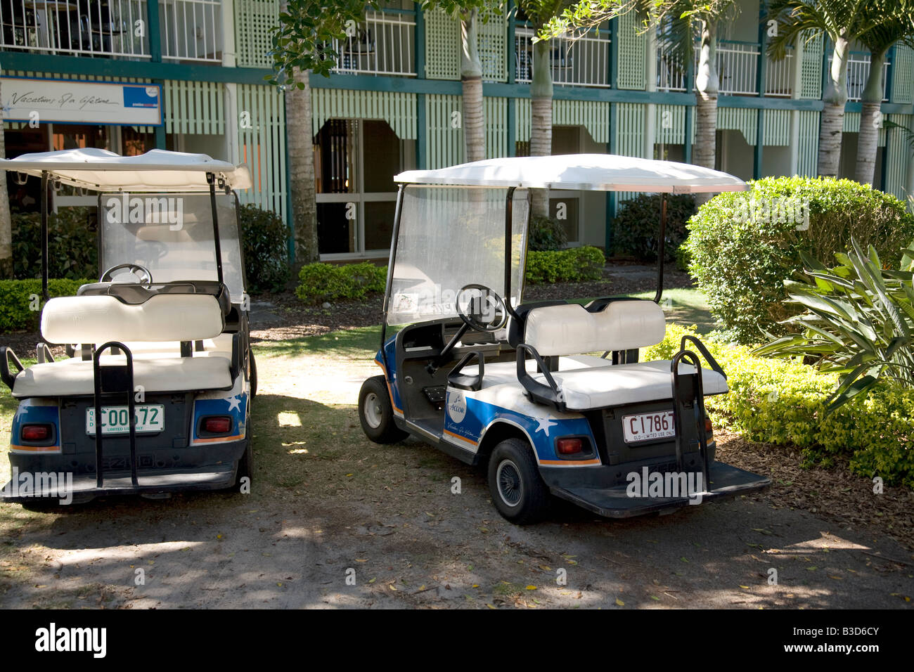 two golf style buggies parked at a resort complex in queensland,australia - Stock Image