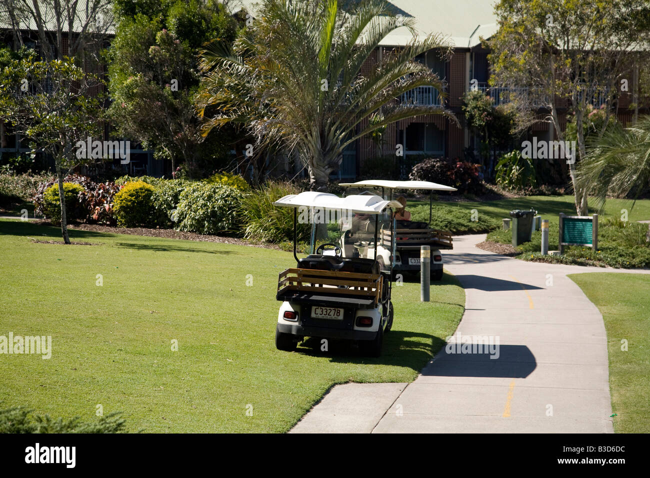 two golf cart leisure buggies parked on the resort complex lawn,queensland,australia - Stock Image
