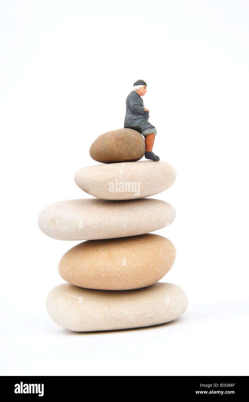 Old woman on pile of pebbles - alone / loneliness / abandoned / balance / life / solitude / isolation / stability - Stock Image