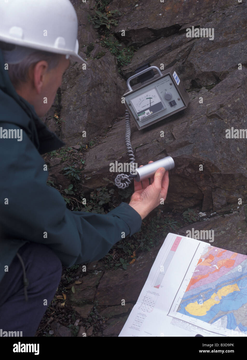 A geologist uses a geiger counter while examining rocks Stock Photo