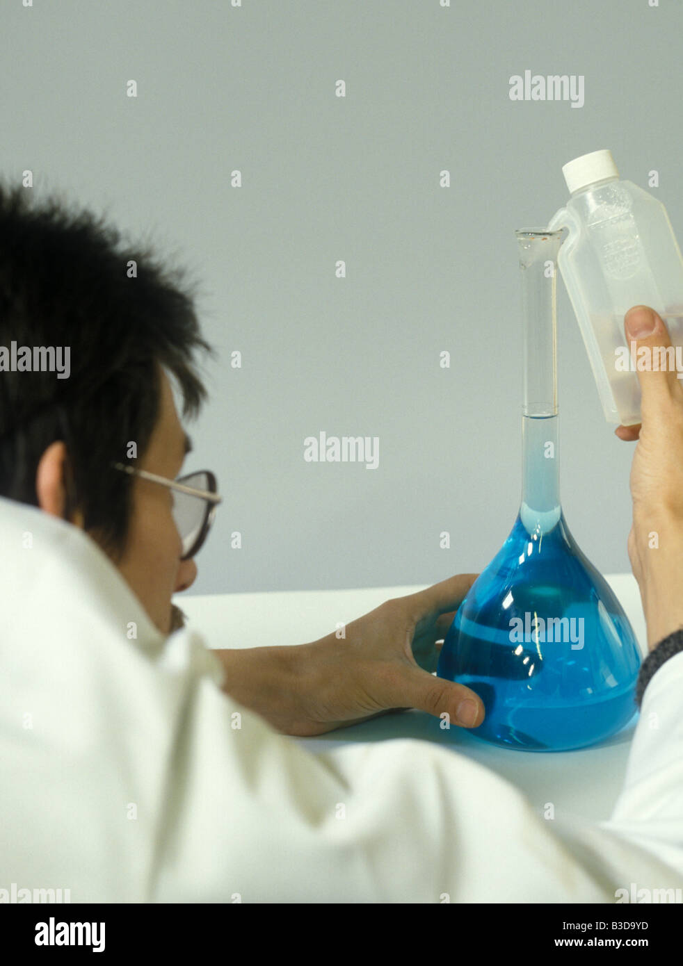 A lab technician carefully brings the meniscus up to the mark Stock Photo