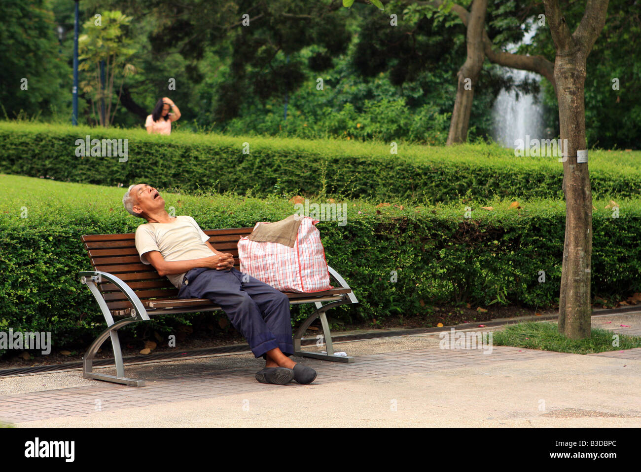 Man snoozes on a bench in a public park in Kowloon, Hong Kong - Stock Image