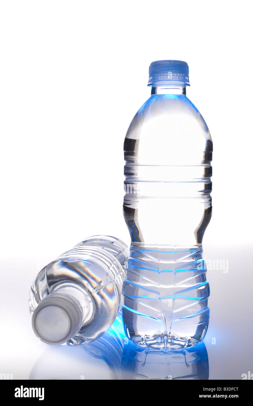 Two clear eco plastic bottles of drinking water. One upright and one laying down. White background. - Stock Image