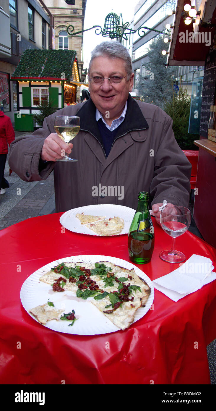 Christmas market in Wuppertal-Elberfeld, food and drink, man stands at a bar table and drinks a toast to the photographer - Stock Image