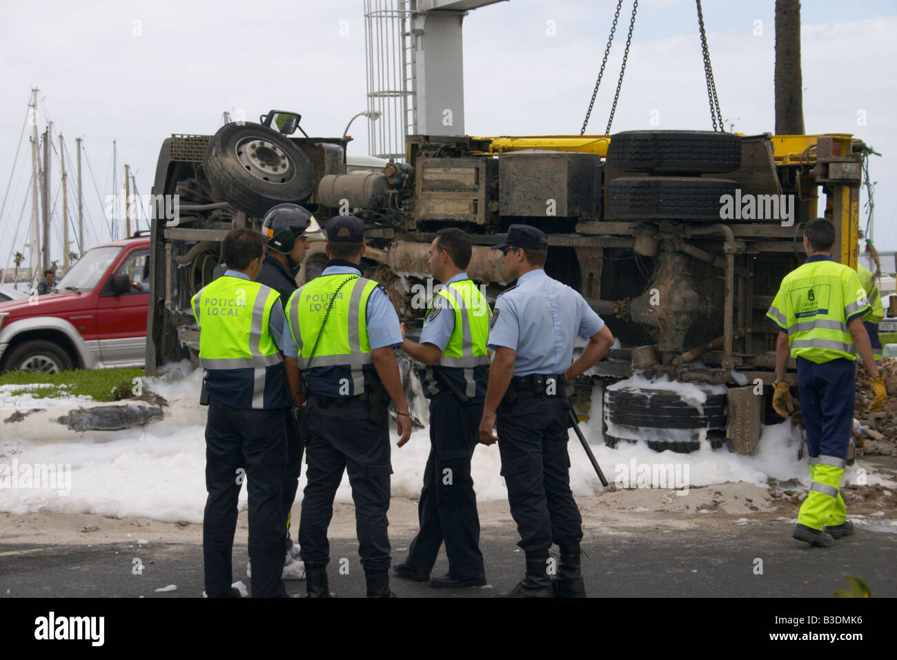Police and fireman at scene of road traffic accident on Gran Canaria with foam and sand on road. Stock Photo