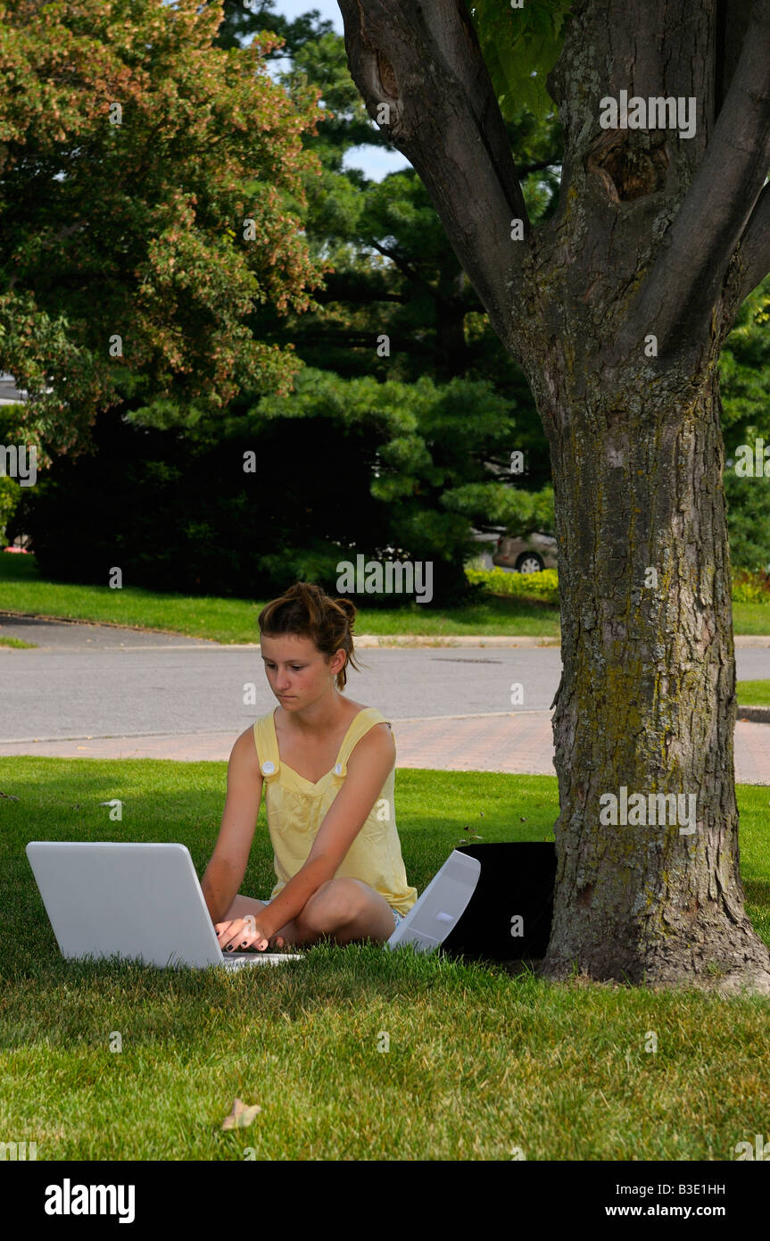 Young girl doing homework on a laptop in the front yard under a maple tree - Stock Image