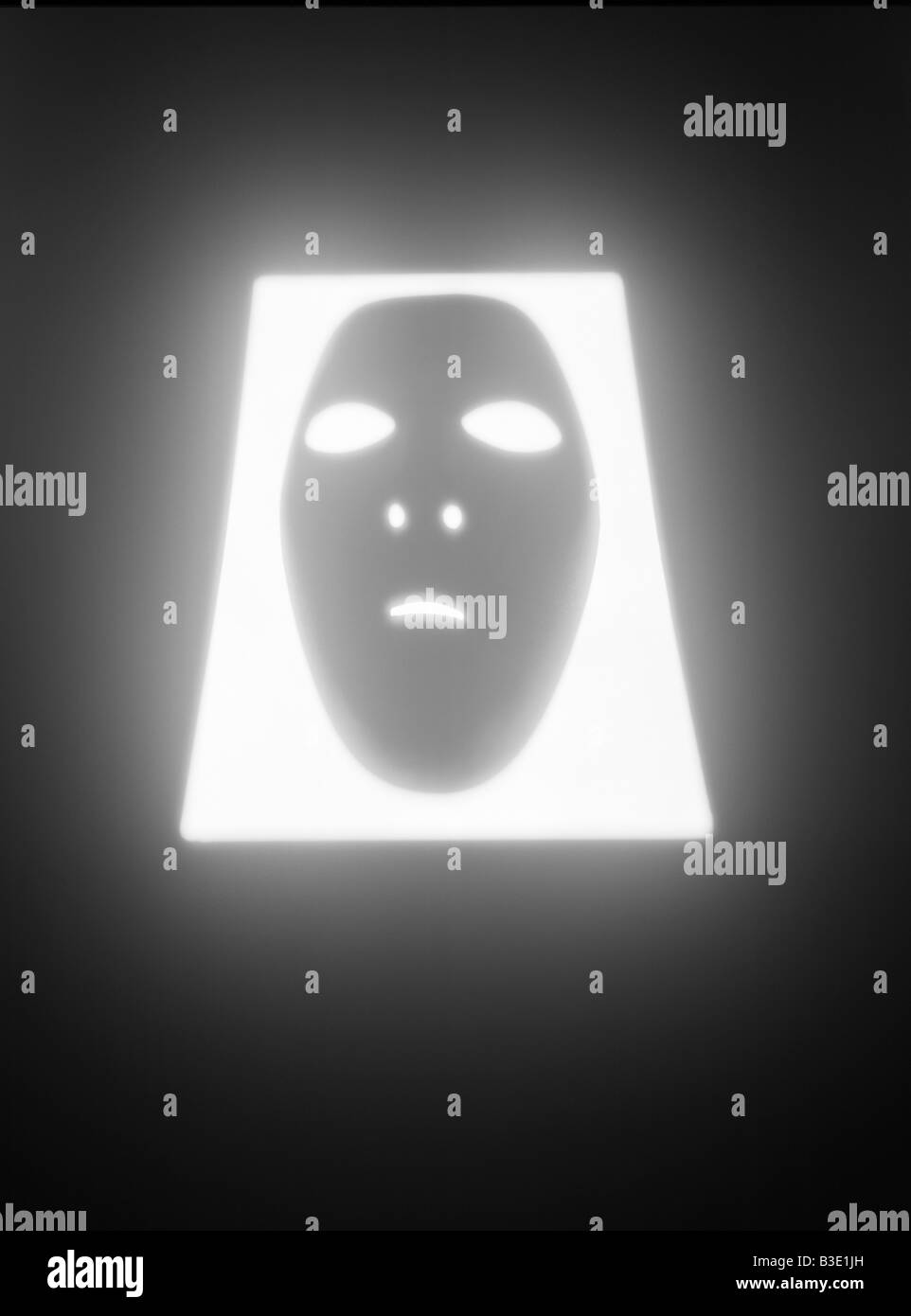 A  human face mask glowing in a rectangular shaped hole - Stock Image
