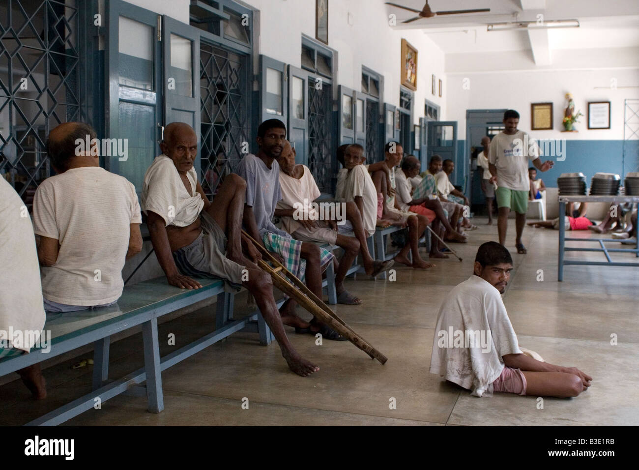 Men with various illnesses sit on the veranda of the Prem Dan Home for the Sick and Elderly in Kolkata, India. - Stock Image