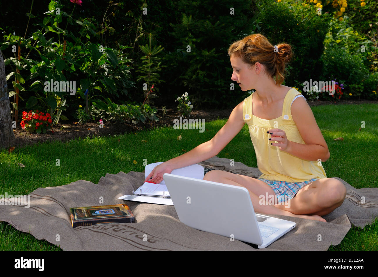 Teenager doing homework with laptop outdoors on a blanket in the back yard in the shade of a tree - Stock Image