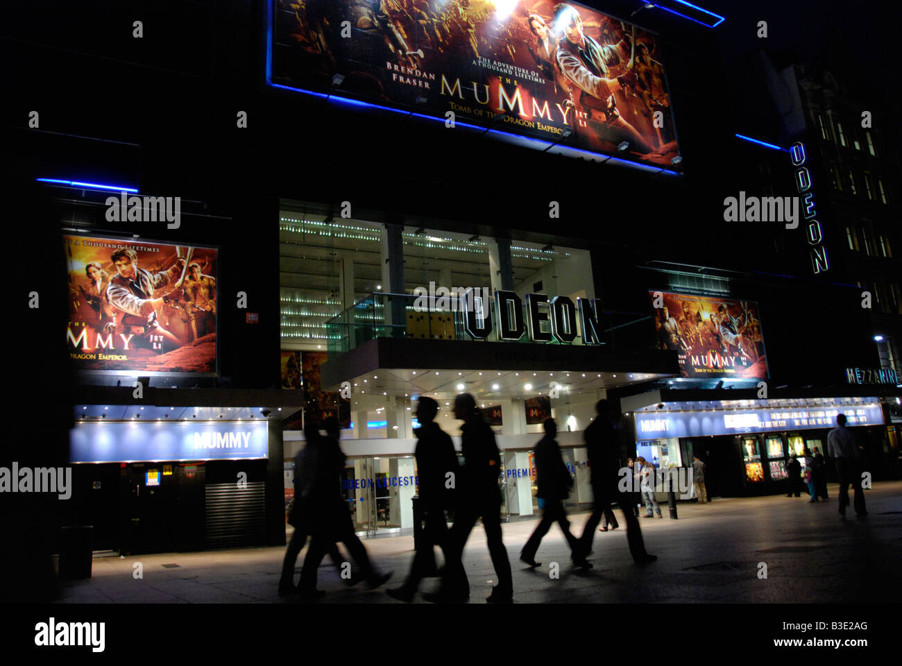 People passing the Odeon Leicester Square cinema at night London England - Stock Image