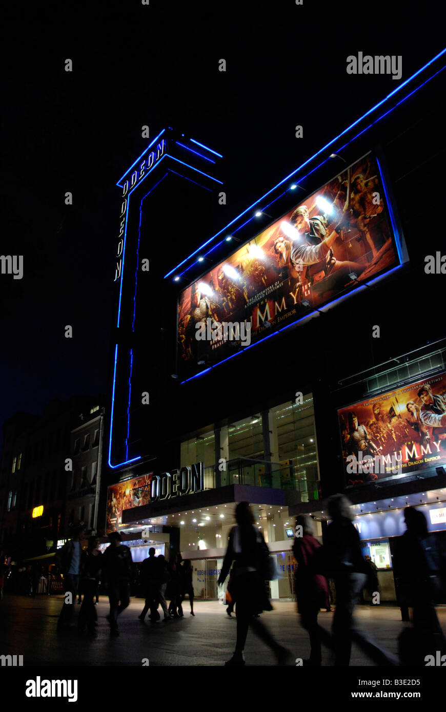 Women passing the Odeon Leicester Square cinema at night London England - Stock Image