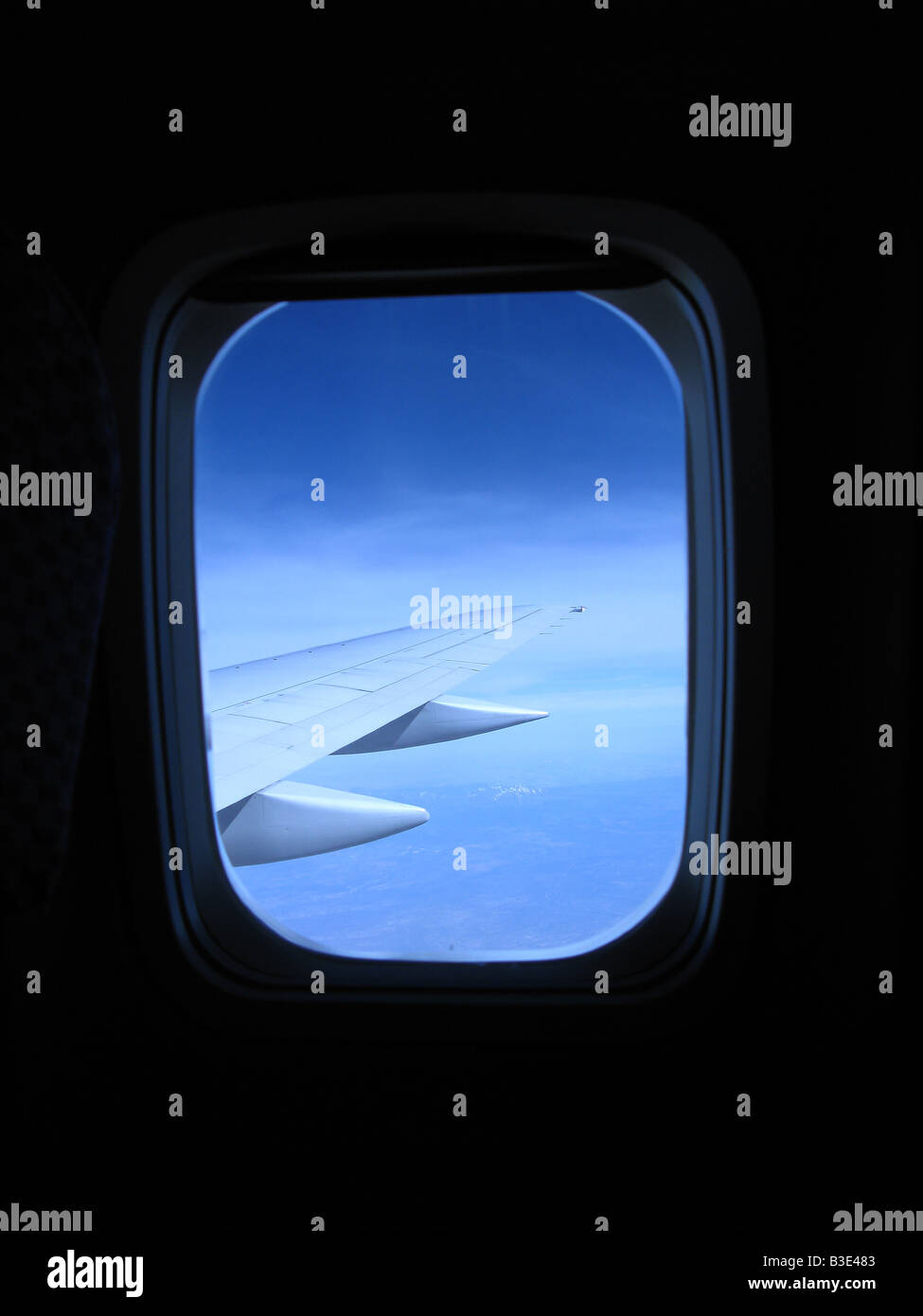 Looking out an airplane's cabin window with a view of the wing and blue sky Stock Photo