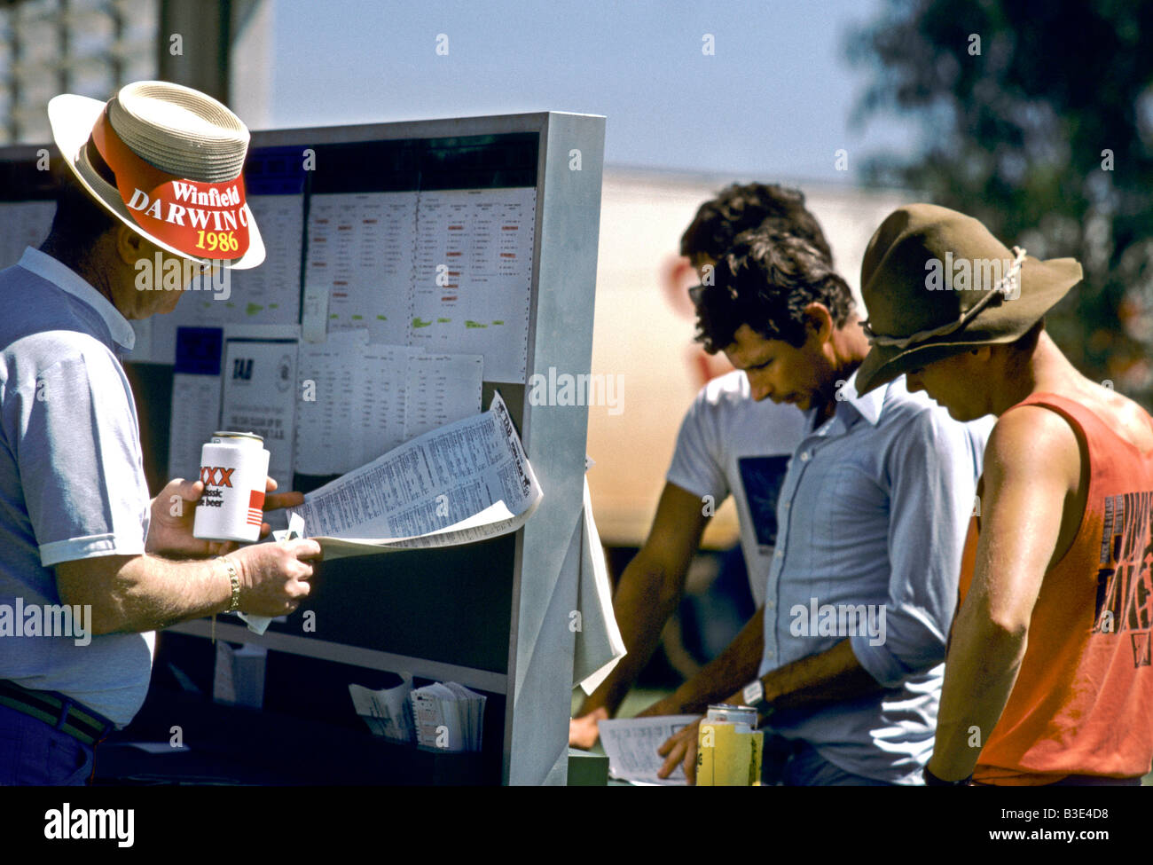 MEN ON A SUNNY DAY AND LOOKING AT A BOARD AND RACE CARD AT A HORSE RACE ONE MAN WEARS A STRAW BOATER, PERTH 1986 - Stock Image