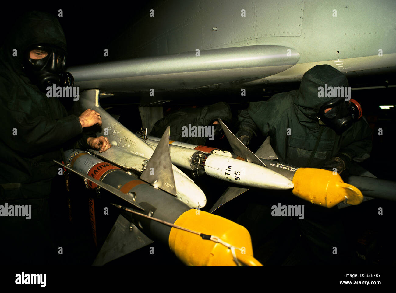 GROUND CREW WEARING GAS MASK NBC NUCLEAR BIOLOGICAL CHEMICAL PROTECTIVE SUITS LOADING MISSILES ONTO PHANTOM JET - Stock Image