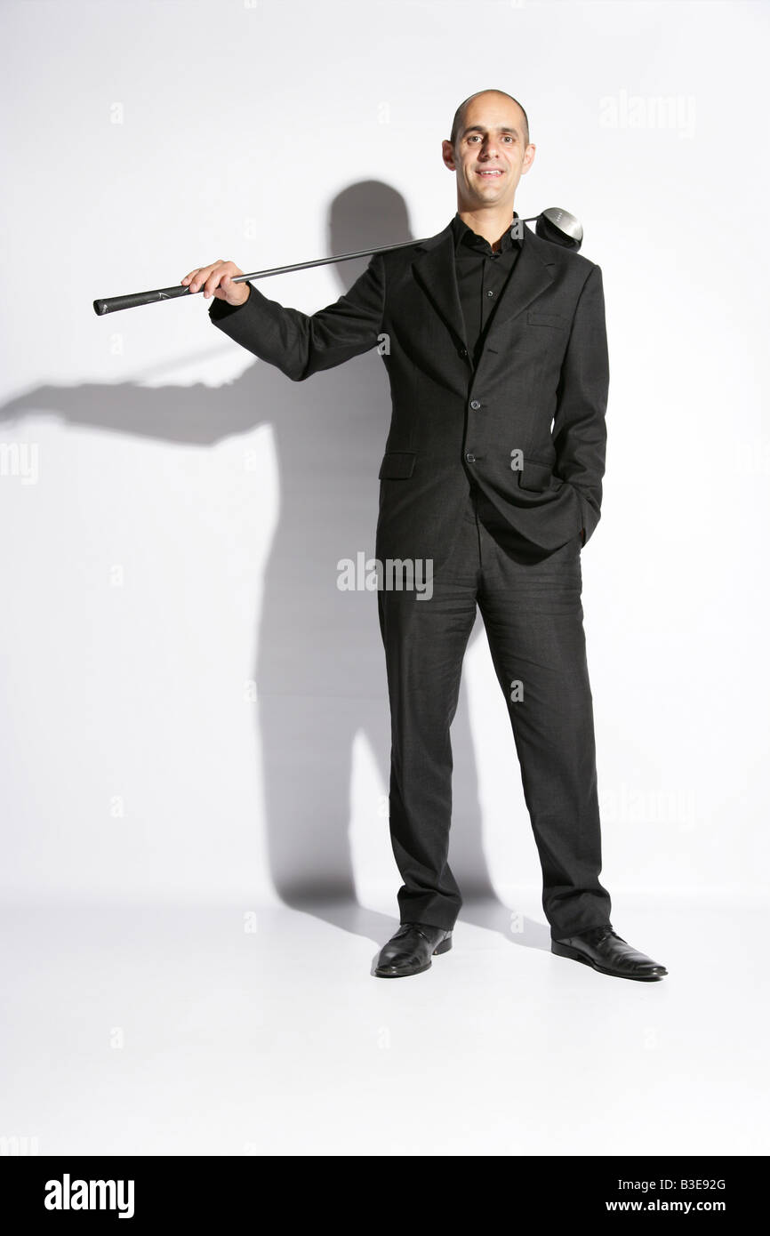 Forty year old man in a business suit holding a golf club stock forty year old man in a business suit holding a golf club publicscrutiny Images