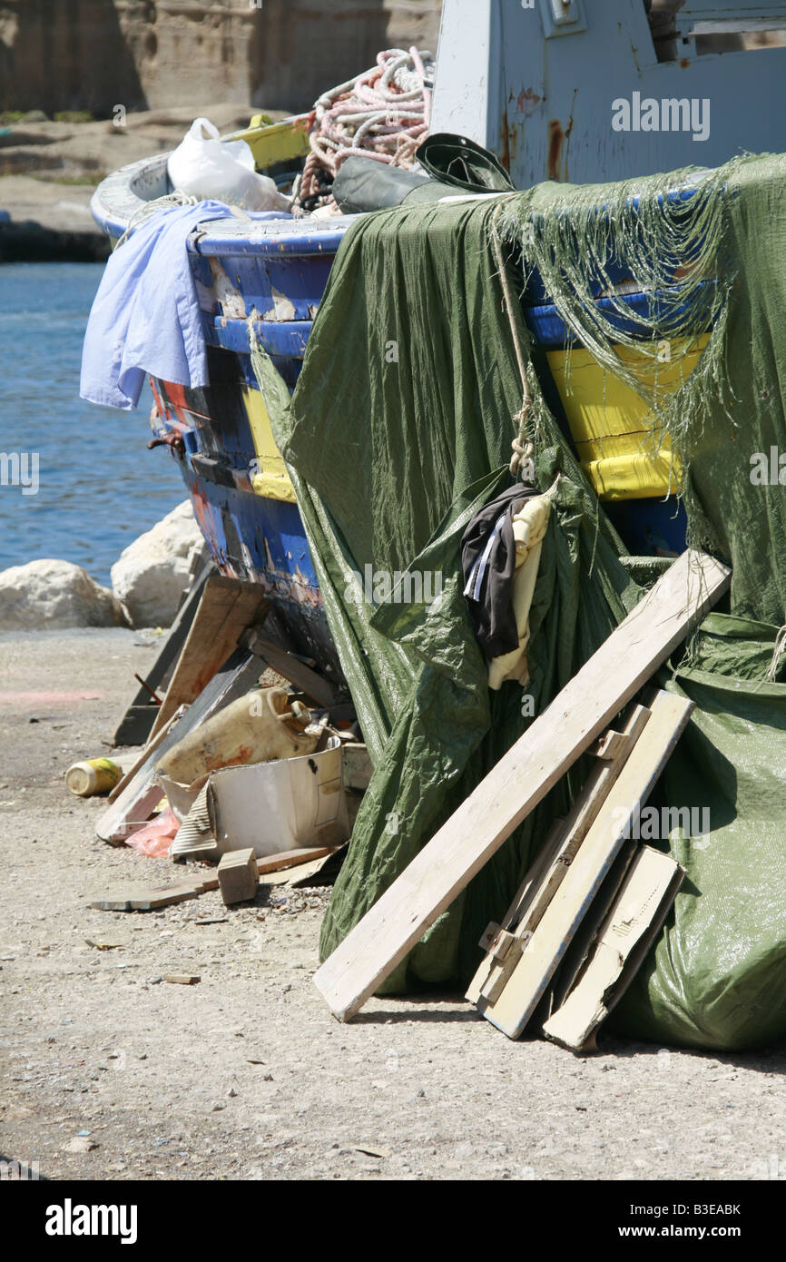 old fishing boat with tarpaulin cover on dry land in sun Stock Photo