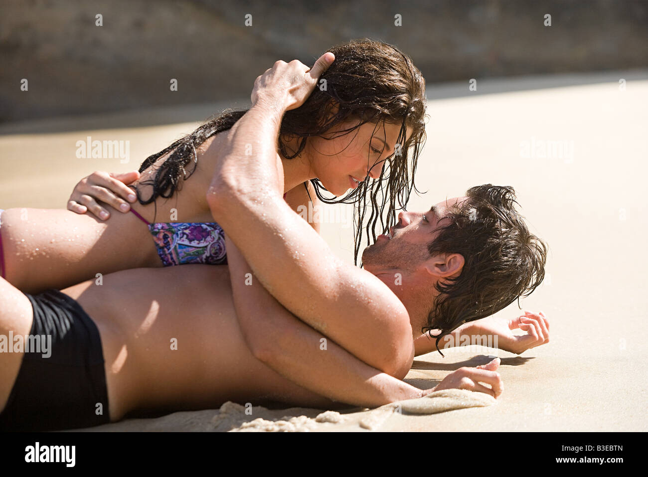Intimate couple lying on a beach - Stock Image