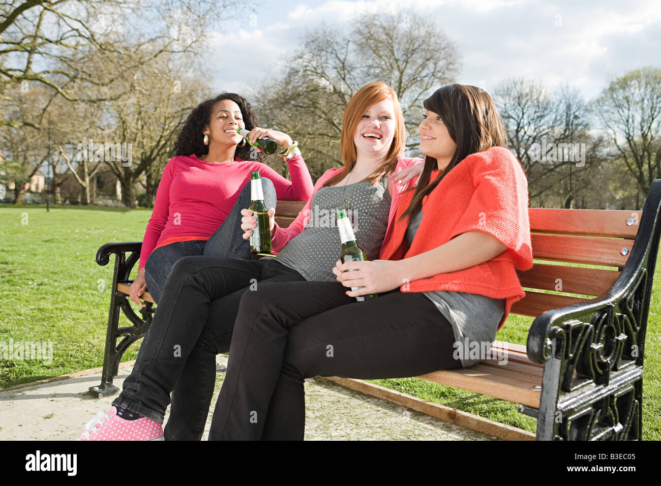 Girls on bench drinking beer - Stock Image