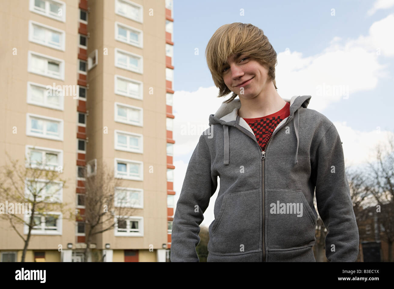 Teenage boy by tower block - Stock Image