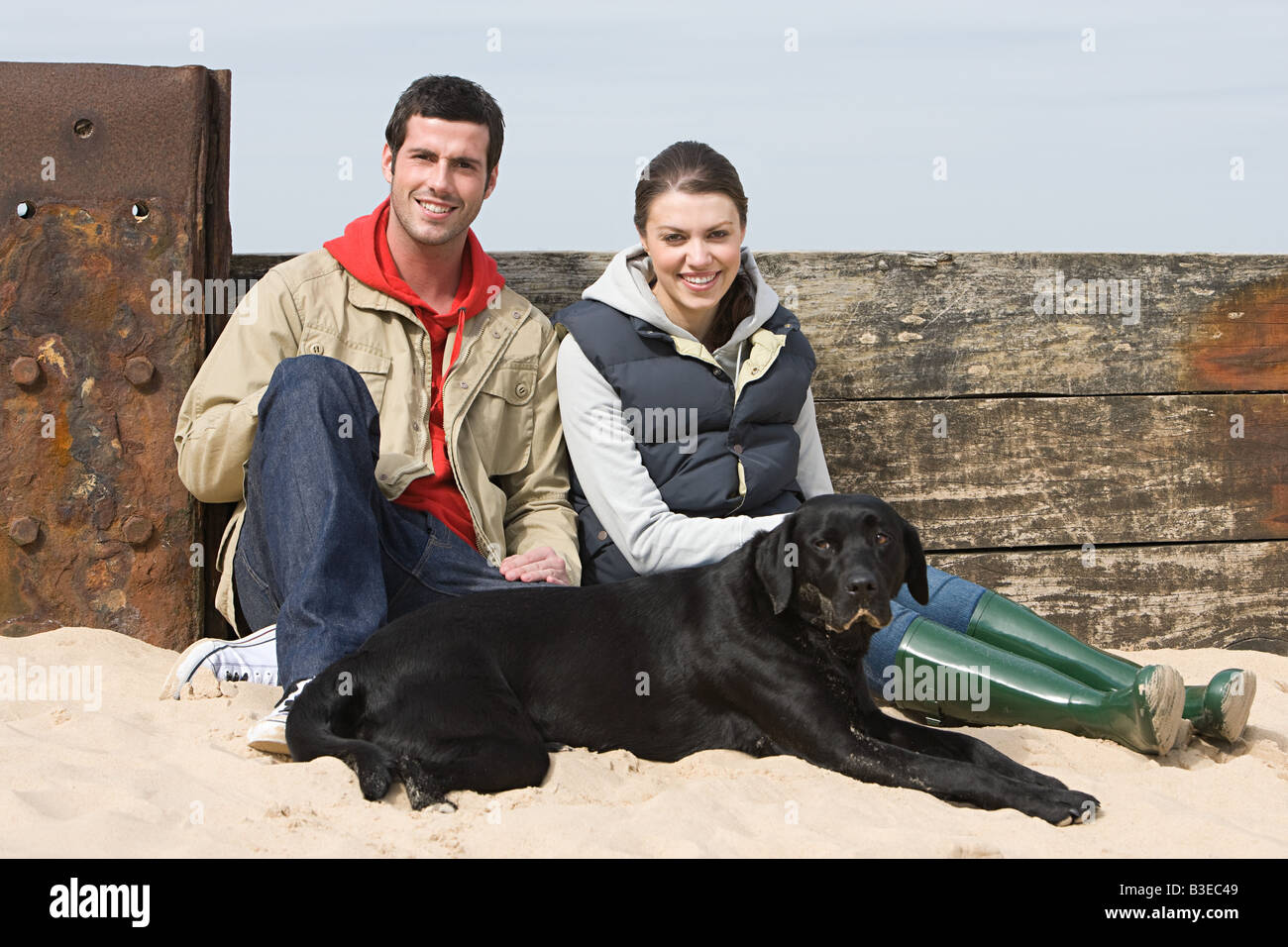 Couple sitting with pet dog at beach - Stock Image