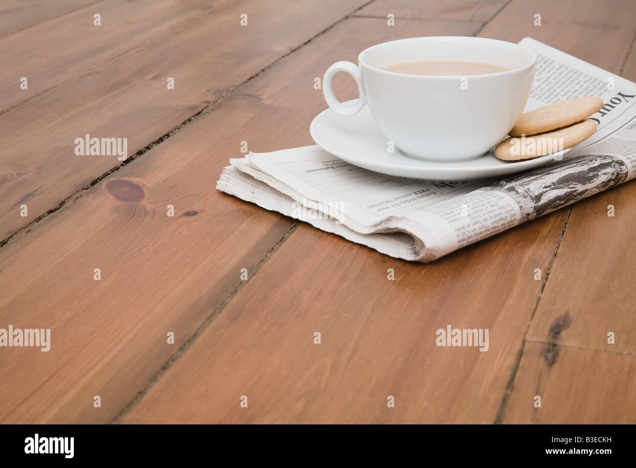 Tea and newspaper on floor - Stock Image