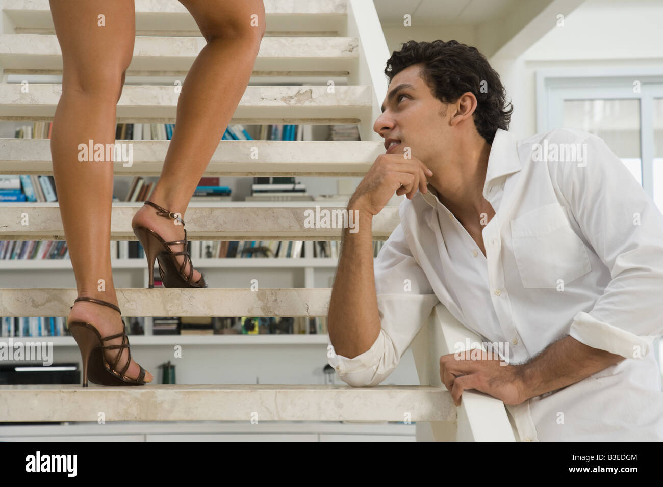 Man looking at a womans legs - Stock Image