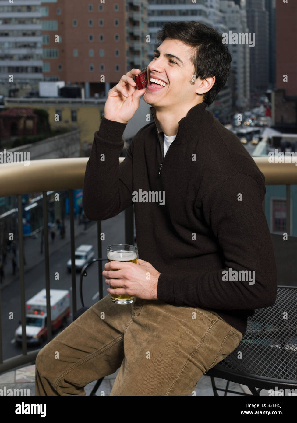 Man with cellphone and beer - Stock Image