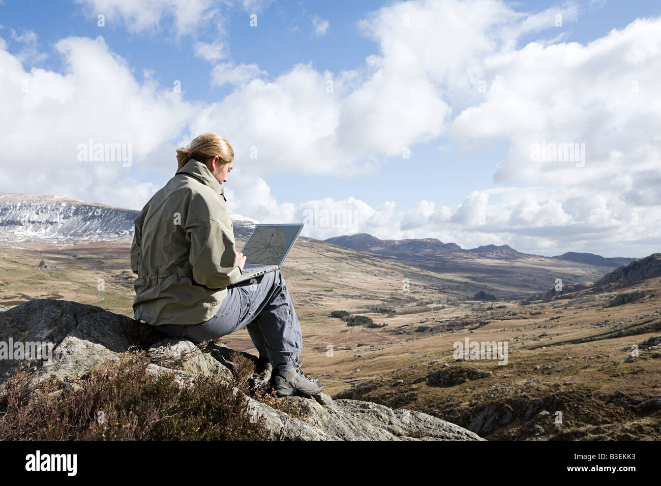 A woman sat on a rock using a laptop - Stock Image
