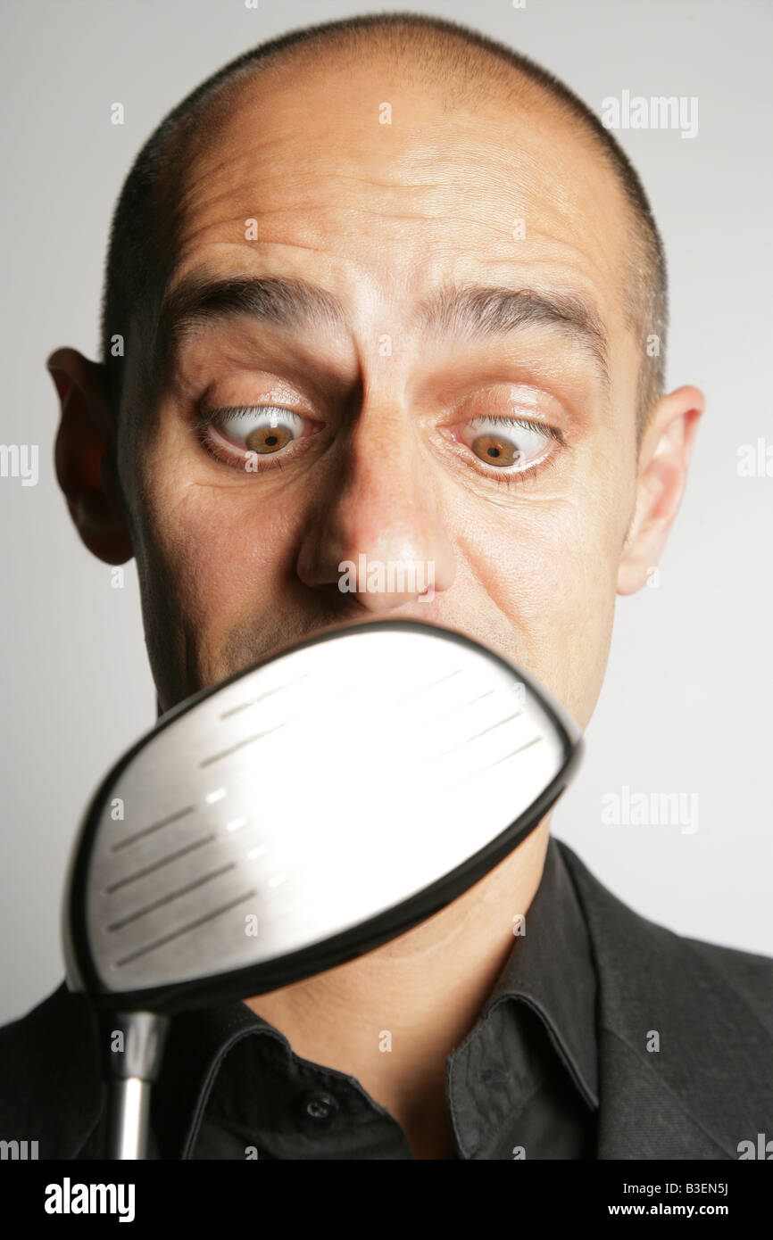 forty year old man looking cross eyed at golf club stock. Black Bedroom Furniture Sets. Home Design Ideas
