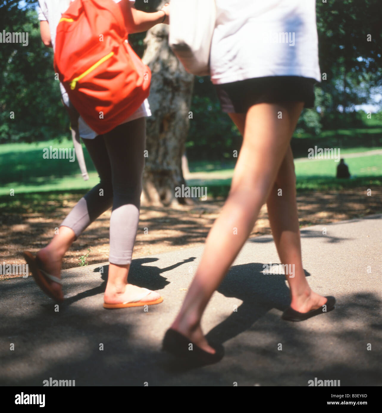 52d5d4e2b6a The blurry legs of two young women walking with rucksacks and wearing  flipflops in Central Park