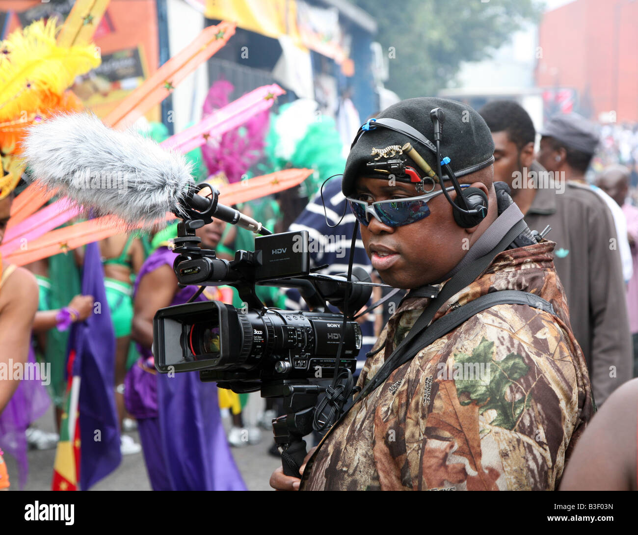 A black man wearing sunglasses, beret and camouflage uses a video camera to film the Notting Hill Carnival - Stock Image