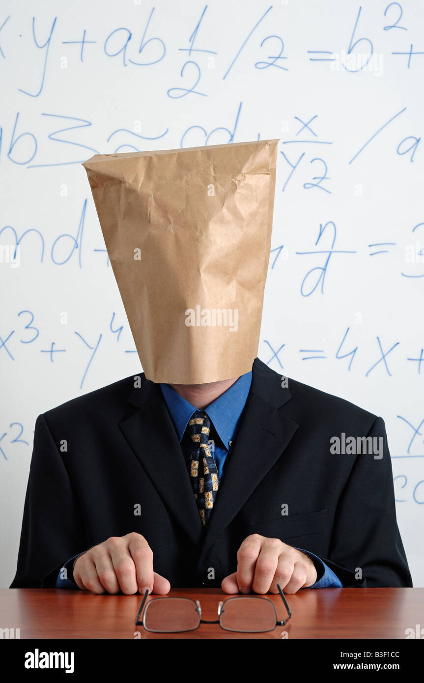 Man in a Suit with a Brown Paper Bag on His Head Sitting Behind His Desk - Stock Image