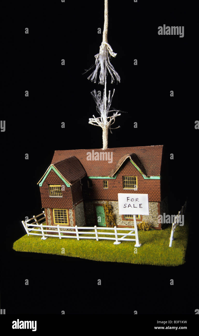 home for sale dangling on rope with strands about to break concept picture illustrating changing nature of housing - Stock Image